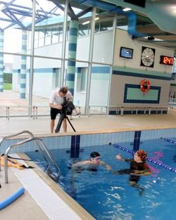 Il regista Alberto Nacci riprende una seduta della riabilitazione in piscina di Marcello Salvi con il fisioterapista