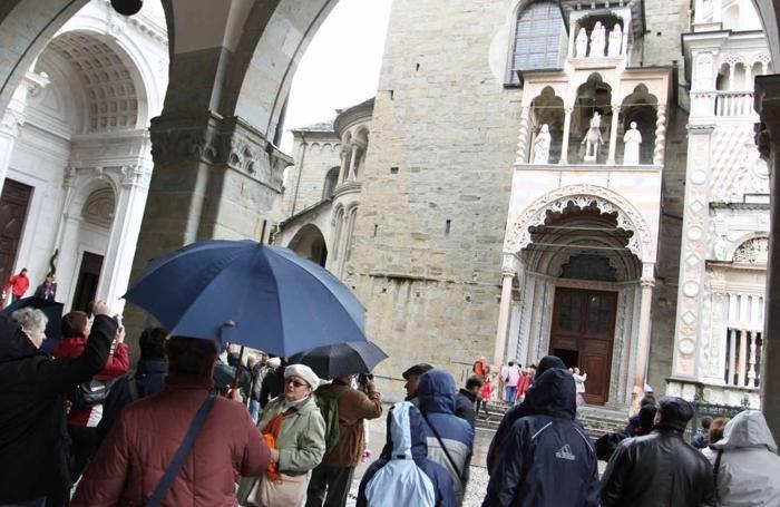 Turisti ed ombrelli sotto il Palazzo della Ragione