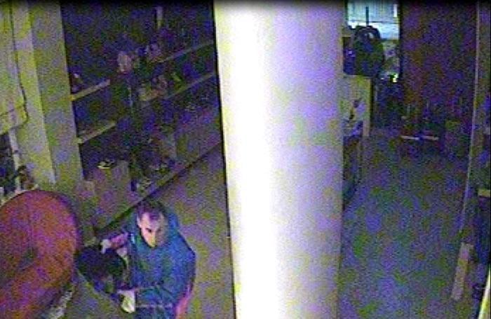 Un'immagine della videosorveglianza con un malvivente all'opera all'interno del negozio di via Roncalli a Gazzaniga