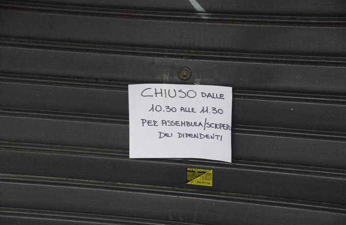 Il cartello sulla serranda durante l'assemblea dei dipendenti
