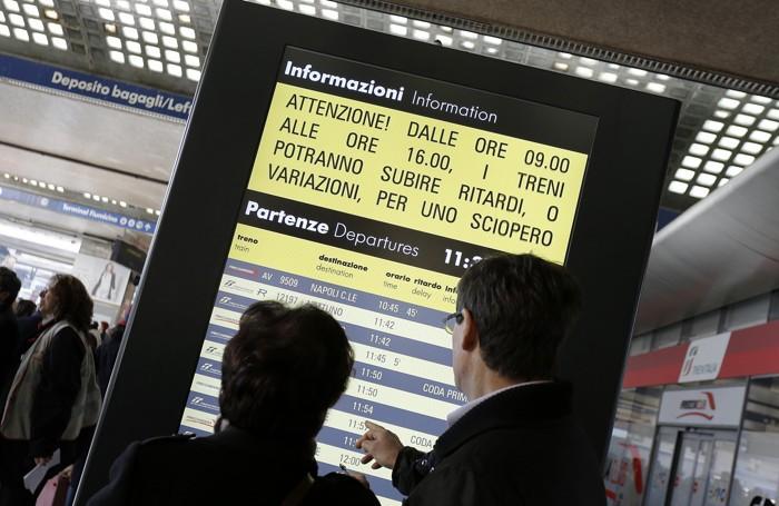 Viaggiatori alla stazione Termini di Roma consultano l'orario dei treni durante lo sciopero generale indetto dai sindacati
