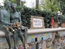 Muretto di Alassio con la statua di due fidanzati e i lucchetti lasciati dalle coppie