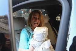 Michelle saluta i fotografi e le persone a fine Battesimo