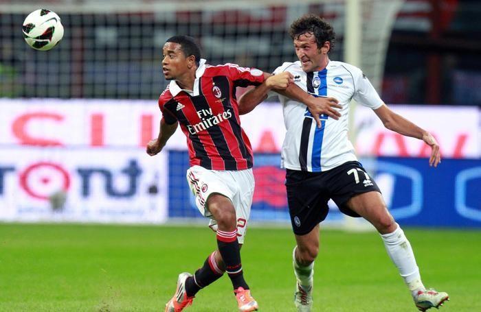 Emanuelson in maglia rossonera, contrastato dall'atalantino Raimondi.