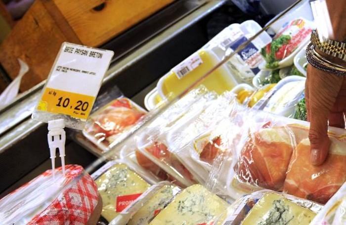 Una donna fa la spesa all' interno di un supermercato