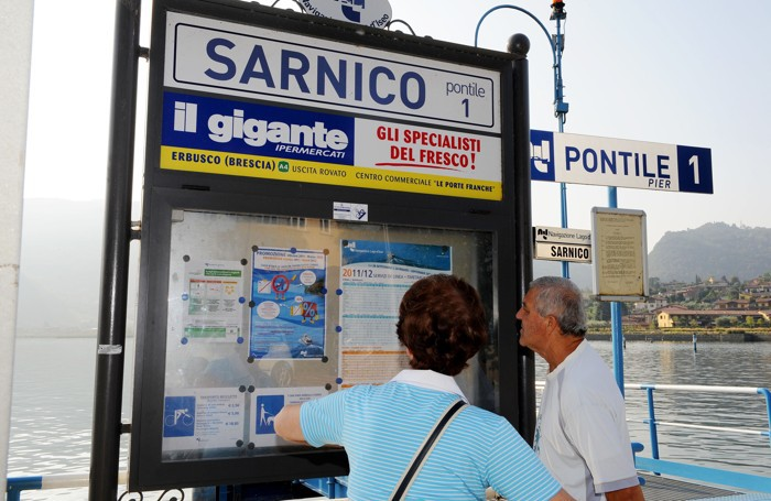Una coppia di turisti controlla l'orario dei battelli all'imbarcadero di Sarnico