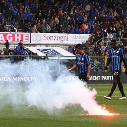 I giocatori escono dal campo a fine partita, la  torcia è stata lanciata dai tifosi
