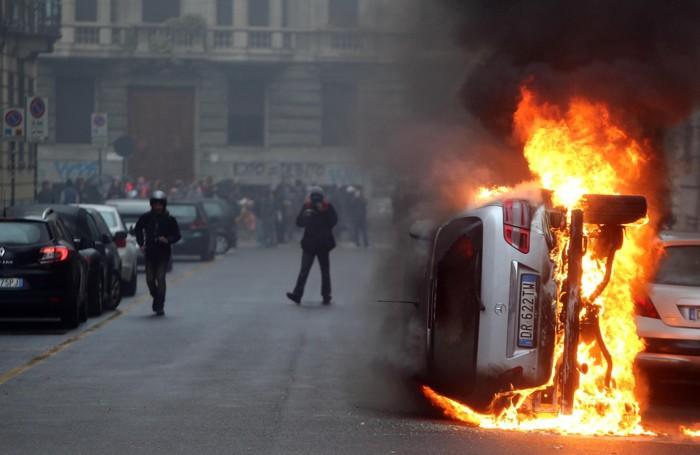 Un'auto va a fuoco durante gli scontri a Milano