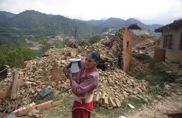 Un'anziana tra le macerie del terremoto
