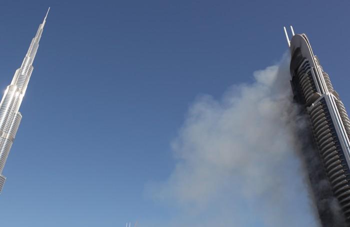 Il fumo che esce dall'«Address Downtown» a Dubai. A sinistra il  Burj Khalifa, il grattacielo più alto del mondo.