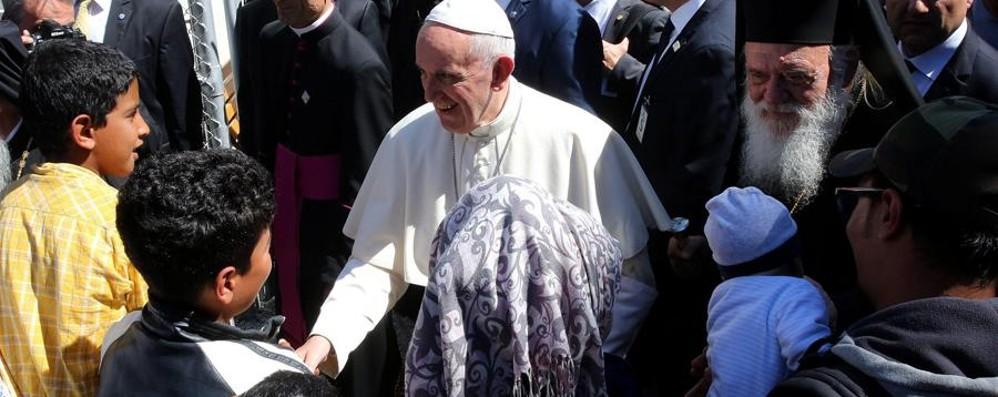 Il Papa a Lesbo per abbracciare i profughi «Non siete soli». E  rientra con 12 di loro