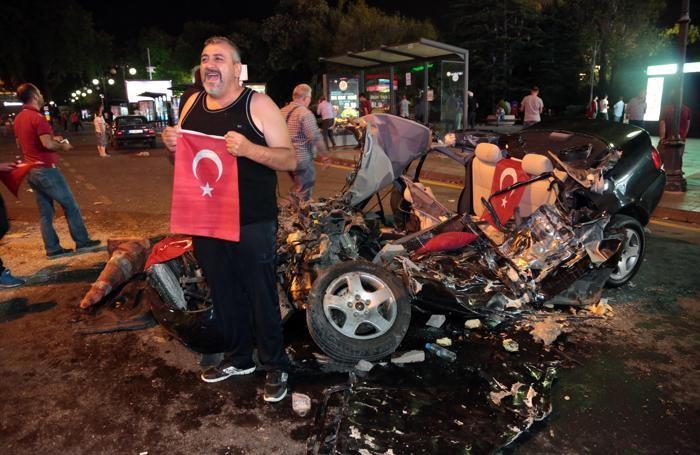 Un uomo posa con la bandiera della Turchia vicino a un'auto schiacciata da un tank militare