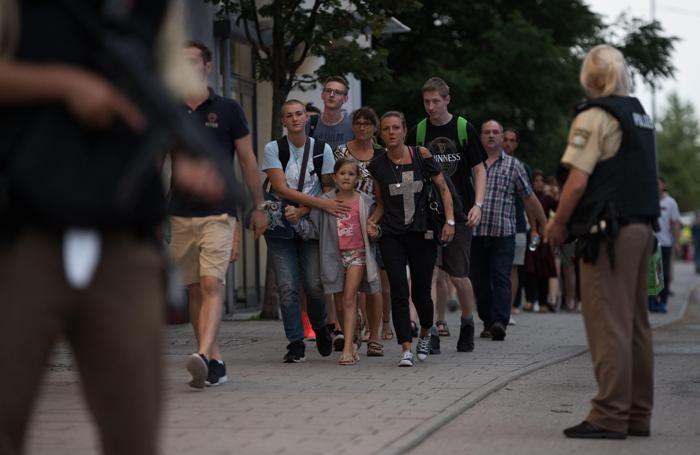 La polizia scorta la gente che esce dal centro commerciale