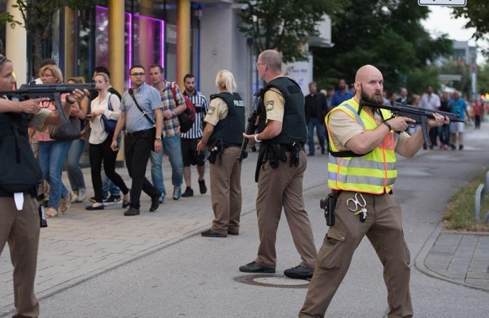Polizia scorta la gente che esce dal centro commerciale