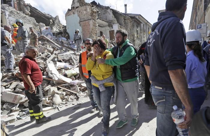 Una donna è confortata dai soccorritori