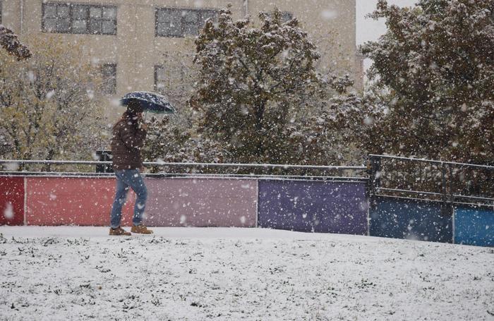 Un uomo cammina mentre nevica a Bologna