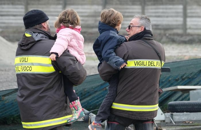 Italian firefighters brings to safety two children evacuated in Lentigione, a hamlet of Brescello