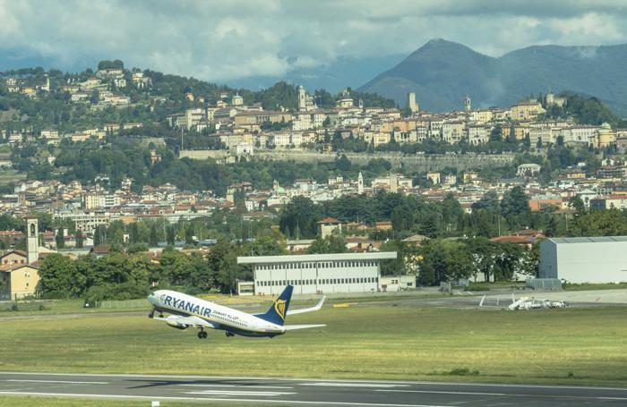pista di decollo aeroporto di orio al serio e panorama di città alta - ryanair