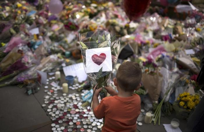 A child places flowers in a square in central Manchester, Britain, Wednesday, May 24, 2017, after the suicide attack at an Ariana Grande concert that left more than 20 people dead and many more injured, as it ended on Monday night at the Manchester Arena. (ANSA/AP Photo/Emilio Morenatti) [CopyrightNotice: Emilio Morenatti]