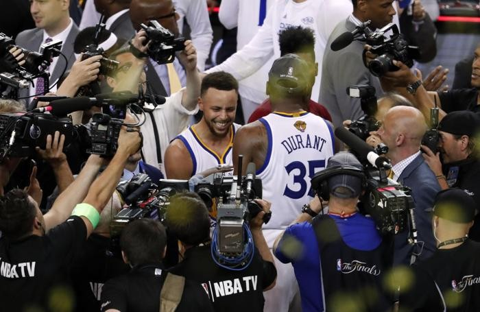 epa06025399 Golden State Warriors guard Stephen Curry (L) and forward Kevin Durant (R) celebrate after the Warriors defeated the Cleveland Cavaliers in game five of the NBA Finals basketball game at Oracle Arena in Oakland, California, USA, 12 June 2017. EPA/MONICA M. DAVEY