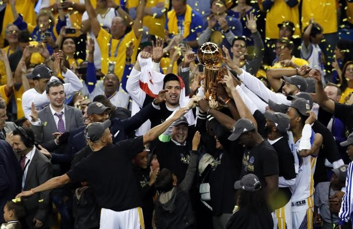 epa06025397 Golden State Warriors players hold the trophy as they celebrate after the Warriors defeated the Cleveland Cavaliers in game five of the NBA Finals basketball game at Oracle Arena in Oakland, California, USA, 12 June 2017. EPA/MONICA M. DAVEY