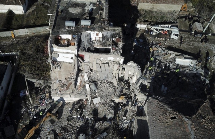 Rescuers search at a damaged building after a magnitude 6.4 earthquake in Thumane, western Albania,