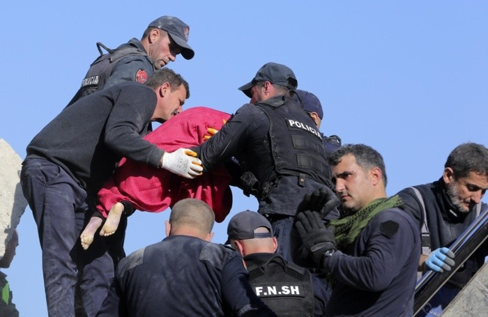 Rescuers hold the body of a five-year old girl after a magnitude 6.4 earthquake in Thumane, western Albania