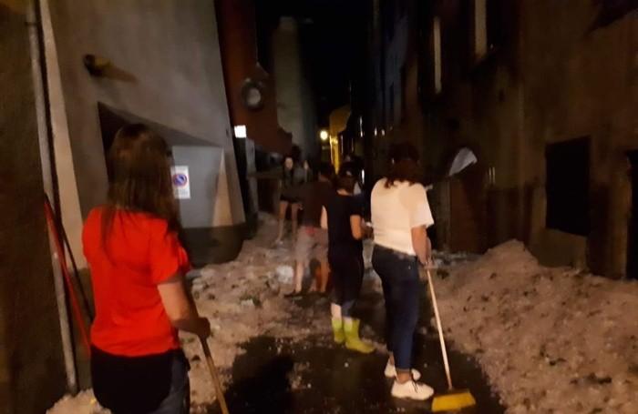 Gente in strada a Vertova per spalare via la tempesta