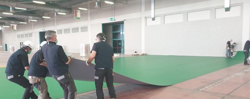Primi lavori alla Fiera di Bergamo Si monta il pavimento dell'ospedale
