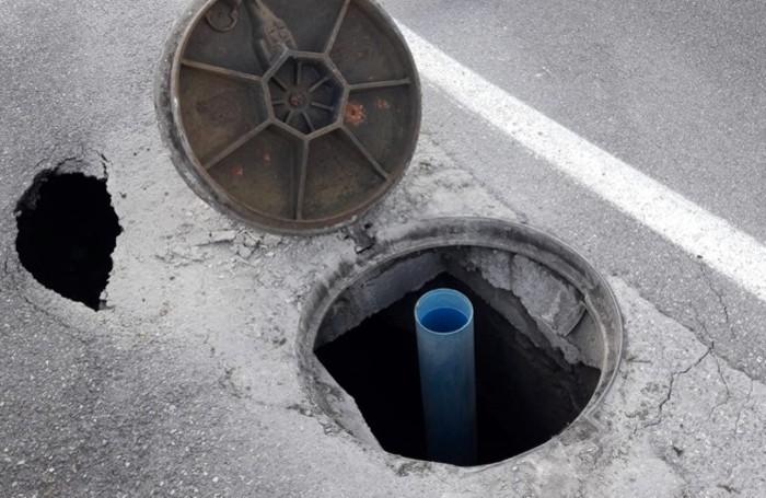 Il buco che si è aperto sul manto stradale in via Gleno