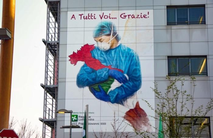 Il messaggio di ringraziamento agli operatori sanitari sulla facciata del Papa Giovanni dell'artista Franco Rivolli